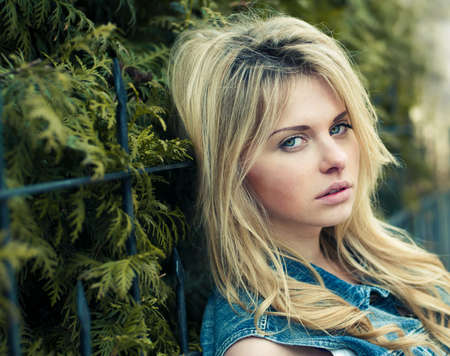 sad girl: pretty girl posing near the fence