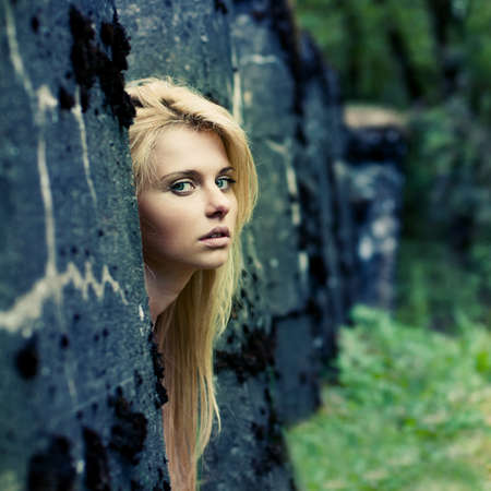 beautiful girl looks out from behind the wall Stock Photo