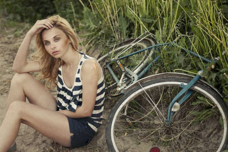 beautiful blonde sitting next to bike photo