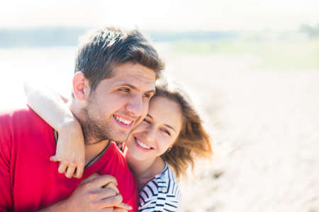 Young man having his woman piggyback on his back under a blue sky on a beach  Couple in love  Stock Photo