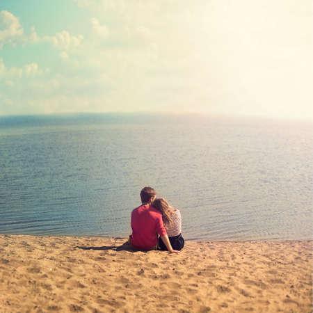 jovenes enamorados: joven pareja se abraza en la arena mirando al mar Foto de archivo