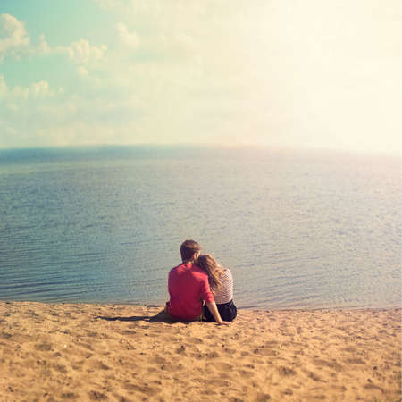 young couple sitting embracing on the sand looking out to sea