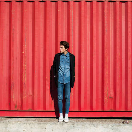 trendy hipster guy in a coat on a red wall