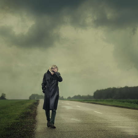 rural landscapes: grim man in a black cloak walking on the road alone  Stock Photo