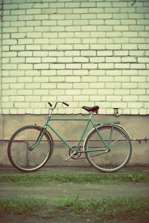 old bicycle against a brick wall