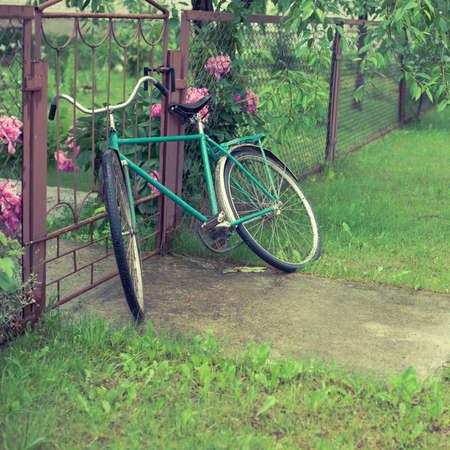old vintage bicycle near the fence Stock Photo