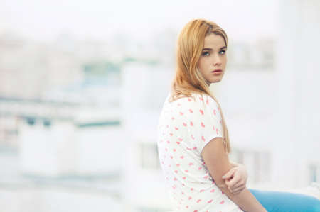 beautiful young girl sitting on the roof of the house Stock Photo - 25985680