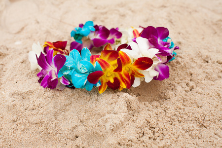 Bright diadem with exotic flowers on the sand