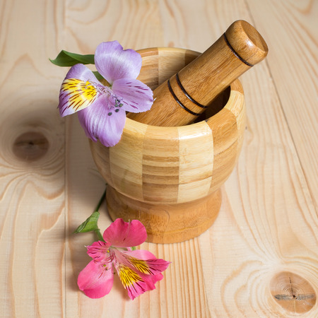 Wooden bamboo pounder with flowers on wooden background