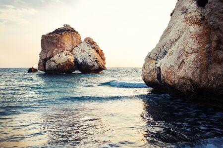 tou: Famous touristic landmark Aphrodites rock and empty pebble beach Petra tou Romiou in sunset, Cyprus