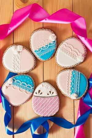 gingery: Easter homemade gingerbread cookie with pink and blue ribbon over wooden table. Colorful image, top view