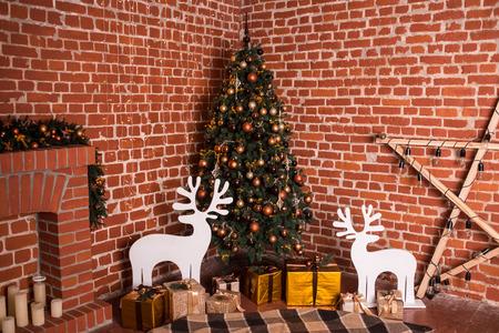 Versierde kerstboom met oranje ballen, gouden geschenken en witte herten. Warme kleuren. Studio horizontale kleurrijke foto