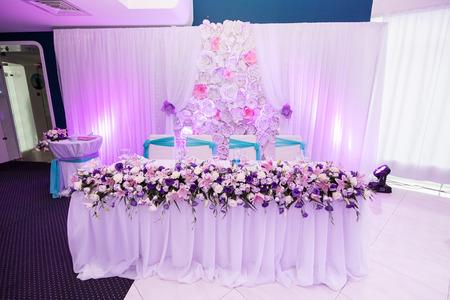 Hermosa mesa de boda con decoración de flores en colores púrpura y rosa azul, blanco en el banquete en el restaurante con flores de papel. Foto horizontal, la luz de color rosa