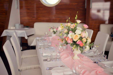 Beautiful wedding table with flower decoration in pastel, peach, white, green and pink colors on the banquet in restaurant. Horizontal photo, pink light