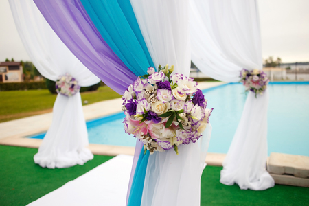 Beautiful romantic wedding arch set up decoration on wedding ceremony in blue, cyan, purple, magenta colors. With flowers and cloth