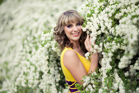 Outdoor spring portrait of a beautiful woman. Attractive girl in white flowers 免版税图像