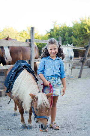 A small smiling girl with curly hair dressed in jeans with a pony at the stable 免版税图像