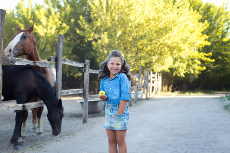 A small smiling girl with curly hair dressed in jeans with a green apple on the stable with horses