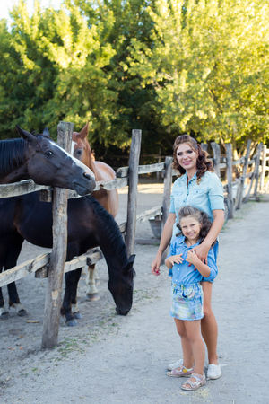 A small smiling girl with mother with curly hair dressed in jeans staying and feeding horses at the stable