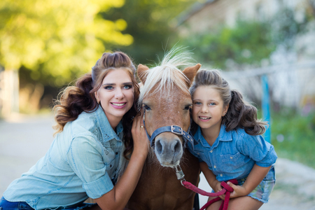 A small smiling girl with a cute pony with mother curly hair dressed in jeans walking at the stable 免版税图像