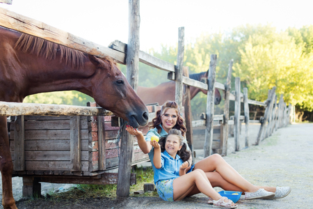 A small smiling girl with mother with curly hair dressed in jeans sitting on the ground near the horse fence at the stable 免版税图像