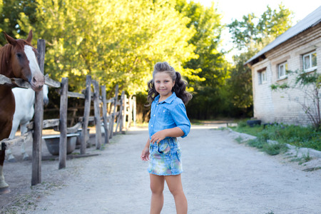 A small smiling girl with curly hair dressed in jeans with at the stable with horses. Colorful horizontal image