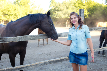 A young smiling woman with curly hair dressed in jeans at the stable with horses. Colorful horizontal image