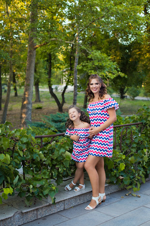 A small smiling girl with curly brown hair dressed in blue red pink dress with zigzag print with young smiling mother staying at vineyard
