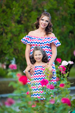 A small smiling girl with curly brown hair dressed in blue red pink dress with zigzag print with young smiling mother staying at rose garden