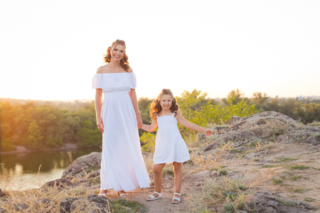 A small smiling laughing girl with curly brown hair dressed white short dress with young beautiful mother in long white dress on the stones at the river on sunset time 免版税图像