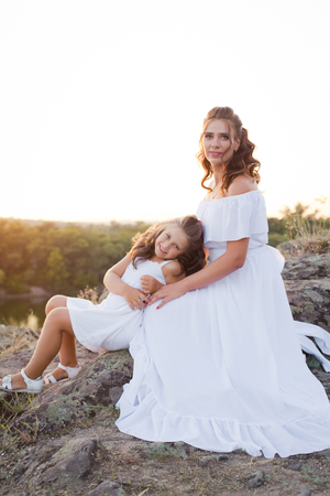 A small smiling laughing girl with curly brown hair dressed white short dress with young beautiful mother in long white dress sitting on the stones at the river on sunset time 免版税图像
