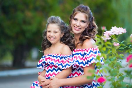 A small laughing girl with curly brown hair dressed in blue red pink dress with zigzag print with young smiling mother sitting at rose garden