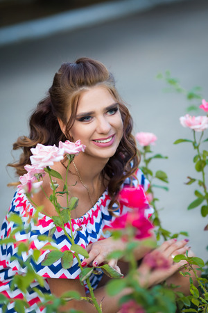 A smiling woman with curly brown hair dressed in blue red pink dress with zigzag print in the rose spring summer garden 免版税图像