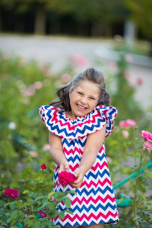 A small smiling girl with curly brown hair dressed in blue red pink dress with zigzag print in the rose garden