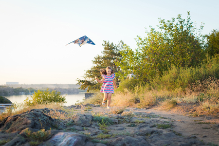 A small smiling girl with curly brown hair dressed in white short dress with red and blue zigzag running and playing with the kite on the stones at the river on sunset time