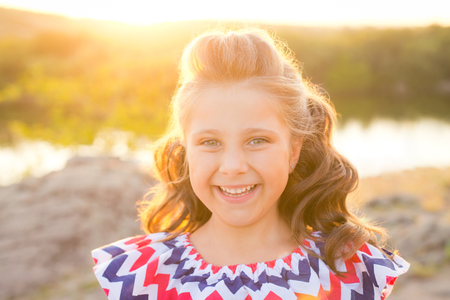 A small smiling girl with curly brown hair dressed in blue red pink dress with zigzag print at the river on sunset time