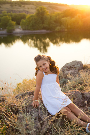 A small smiling girl with curly brown hair dressed white short dress sitting on the stones at the river on sunset time