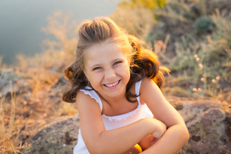 A small smiling laughing girl with curly brown hair dressed white short dress sitting on the stones at the river on sunset time