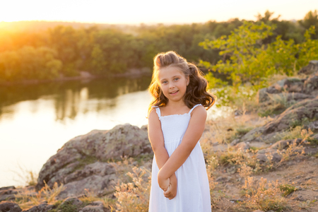 A small smiling laughing girl with curly brown hair dressed white short dress on the stones at the river on sunset time 免版税图像