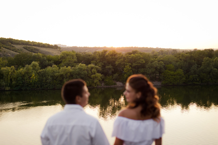 Young beautiful woman in long white dress with her husband on the stones at the river on sunset time