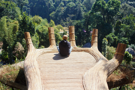 Ecotourism destinations Hoa Son Dien Trang - the Buddha's hand in forest. Tourist sight seeing place in Da Lat, Vietnam. Horizontal images with sitting man in black windbreaker. Ideal for sites, travel agencies, web advertising, banners etc.