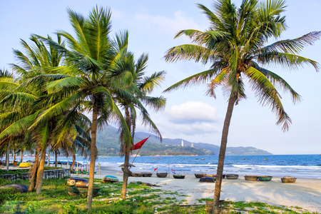 Coconut palm trees at the beach, DaNang, Vietnam. Tranquil clouds and mountains. Blue fishing boats at the send. Colorful horizontal image. Ideal for travel agencies, advertising, banners, web etc