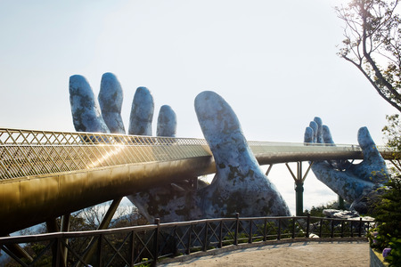 Golden Bridge in hands Da Nang, Vietnam - Ba Na Hills Park. The new symbol of Vietnam. Bright Sunrise at the bridge. Colorful horizontal image of Bana Hills Bridge. Ideal for travel agencies, advertising, banners, web etc