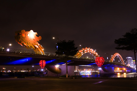 Da Nang, Vietnam: Dragon bridge - the icon of Da Nang city. Famouse fire dragon bridge at the quay. Night colorful horizontal image. Ideal for travel agencies, advertising, banners, web etc