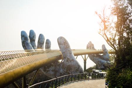 Goldene Brücke in Händen Da Nang, Vietnam - Ba Na Hills Park. Das neue Symbol Vietnams. Heller Sonnenaufgang an der Brücke. Buntes horizontales Bild der Bana Hills Bridge. Ideal für Reisebüros, Werbung, Banner, Web etc.