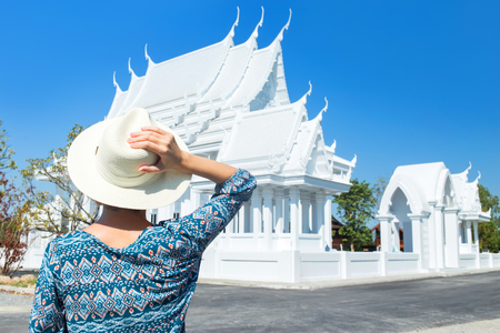 New buddhist pagoda - White Temple in Pattaya city in Thailand. New tourist destination in Pattaya. Blue sky and tranquil landscape. A girl staying back in the hat and blue shirt.Horizontal colorful image ideal for travel agencies, advertising, banners, web etc