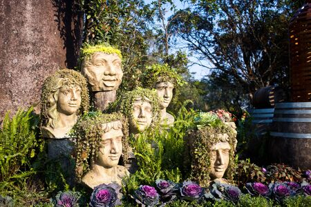 Danang, Vietnam - March 19, 2019. The statue of heads with grass and plants instead of hair - body parts in Ba Na Hills at Da Nang, Vietnam 新闻类图片