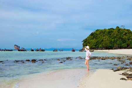 Girl in the hat and white tunic on the Koh Poda island, Krabi, Thailand. Colorful horizontal image with blue sea and cloudy sky, boats and rocks