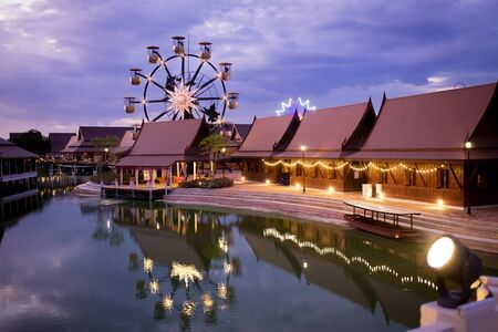 View of Legend Siam park in Pattaya, Thailand. Beautiful Legend Siam is new landmark in Pattaya and popular tourist attraction. carousel, river village and houses, colorful image, sunset dusk view