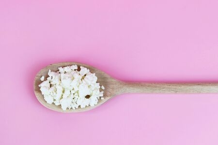 Fresh homemade cottage cheese on a wooden spoon. Copy space - concept of healthy eating, diets, natural food